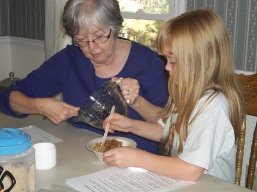 Carolyn is helping her grandma, Carol mix brown sugar scrub.