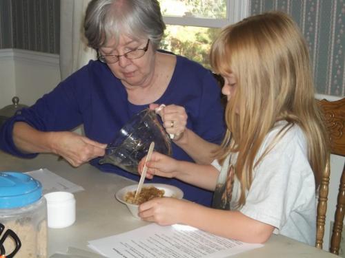 Carolyn is helping her grandma, Carol mix brown sugar scrub.