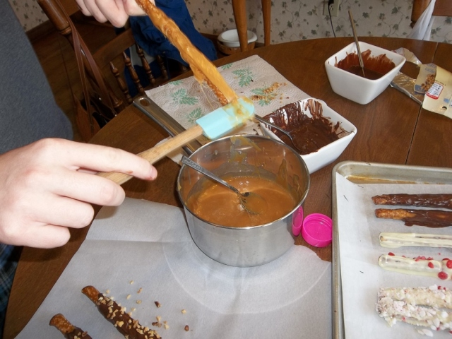Jonathan is coating pretzel with ooey, gooey caramel, mmmm