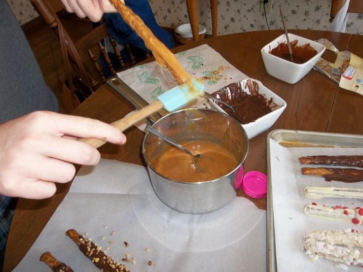 Jonathan is coating pretzel with ooey, gooey caramel, mmmm